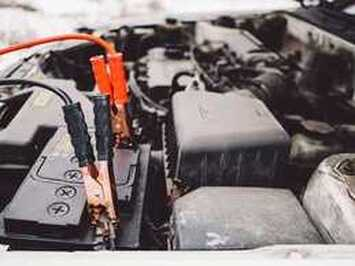 two jumper cables on a car battery
